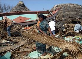 Fisherfolk family in Tamil Nadu picking through the remains of their home