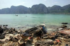 A tsunami-battered fishing boat lies on a beach on Thailand's island of Phi Phi, January 2, 2005, Reuters/Bazuki Muhammad